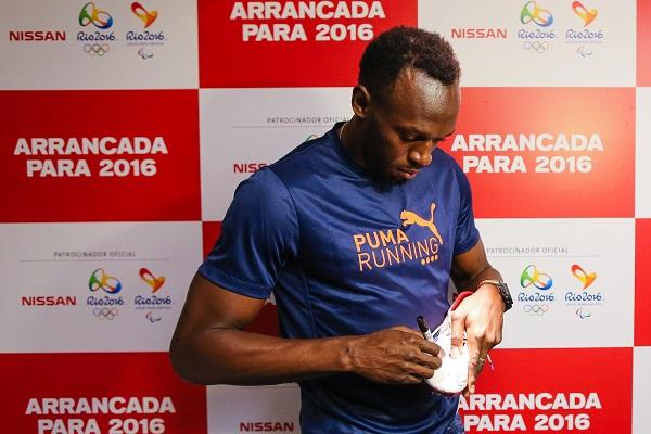 O sobrenatural Bolt autografa as suas sapatilhas.